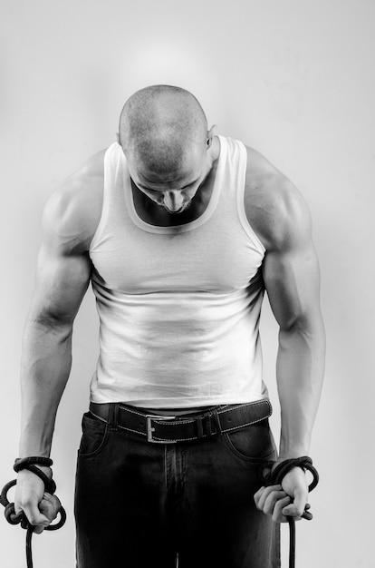 Sportlicher kerl, der auf weißer wand aufwirft. sport, schönheit, schwarzweißfotografie. Premium Fotos