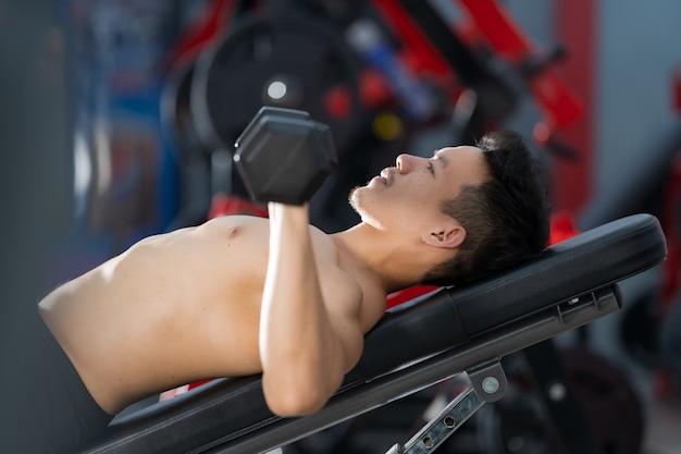 Sportlicher mann, der mit hantel im fitnessstudio trainiert Premium Fotos