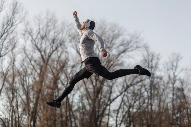 Sportlicher mann der seitenansicht, der in wald springt Kostenlose Fotos