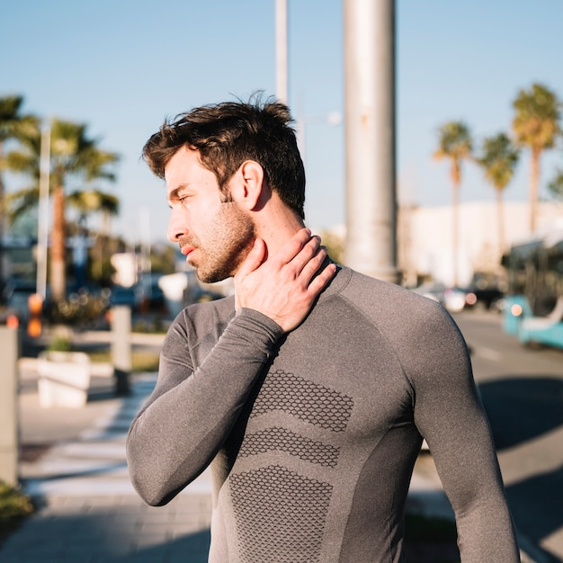 Sportlicher mann, der verletzten hals ausdehnt Kostenlose Fotos