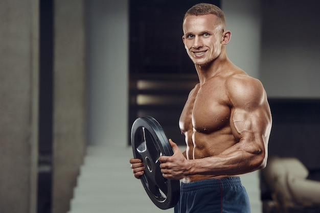 Sportlicher mann des kaukasischen krafttrainings, der bizepsmuskeln aufpumpt. starker bodybuilder mit sixpack, perfekter bauchmuskulatur, trizeps, brust, schultern im fitnessstudio. fitness- und bodybuilding-konzept Premium Fotos