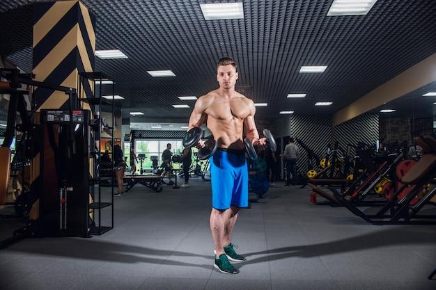 Sportlicher mann mit großen muskeln und einem breiten rücken trainiert in der turnhalle, eignung Premium Fotos