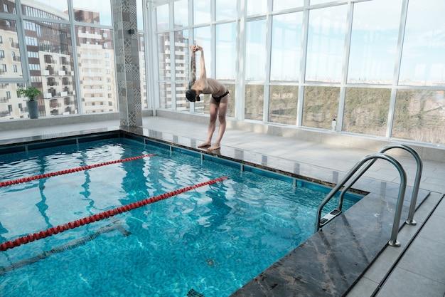 Sportlicher mann mit tätowierung, die am rand des pools steht und arme vor dem schwimmen ausübt Premium Fotos
