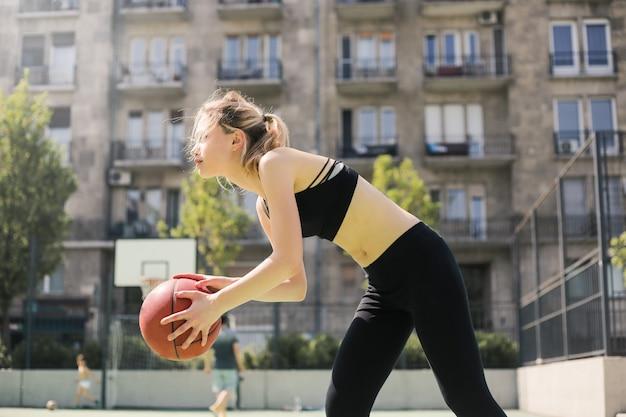 Sportliches mädchen, das basketball spielt Premium Fotos