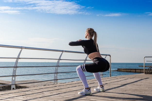 Sportliches mädchen, das hocken nahe dem meer tut Premium Fotos