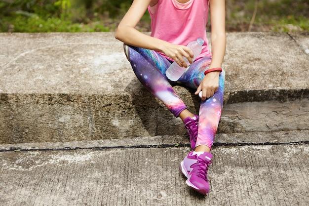 Sportliches mädchen im rosa trägershirt, leggings mit raumdruck und lila laufschuhen, die auf bordstein sitzen und wasser aus der plastikflasche nach cardio-training trinken. sportlerin, die während des trainings im freien hydratisiert Kostenlose Fotos