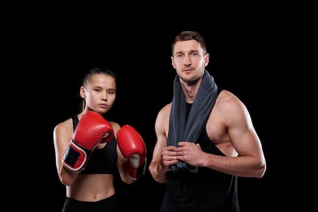 Sportliches mädchen in roten boxhandschuhen und ihrem muskulösen freund mit handtuch, die nahe beieinander stehen Premium Fotos