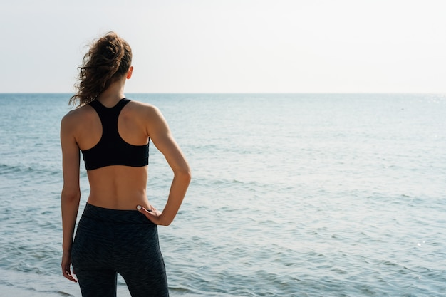 Sportliches mädchen mit dem gelockten haar in einem sport-bh, der auf dem strand steht und morgens das meer betrachtet Premium Fotos