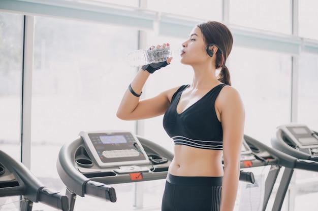 Sportliches trinkwasser der frau asien nach übungen in der turnhalle. Premium Fotos