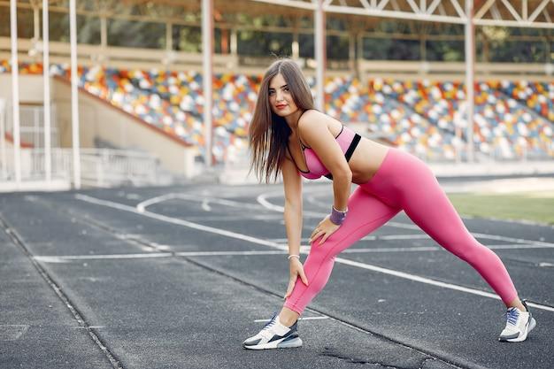 Sportmädchen in einem rosa uniformtraining am stadion Kostenlose Fotos