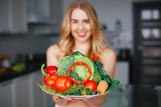Sportmädchen in einer küche mit gemüse Kostenlose Fotos