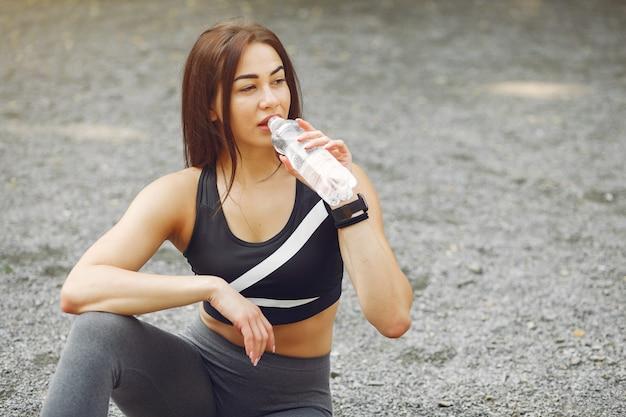 Sportmädchen in sportkleidung ein wasser trinkend Kostenlose Fotos
