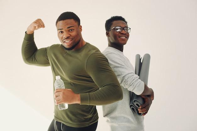 Sportmänner, die auf einer weißen wand stehen Kostenlose Fotos