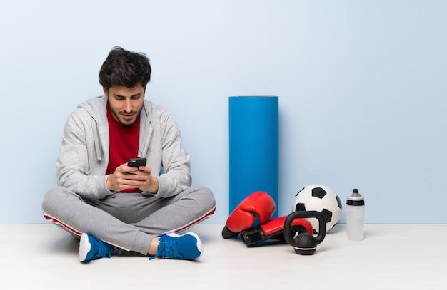 Sportmann, der auf dem boden sendet eine mitteilung mit dem mobile sitzt Premium Fotos