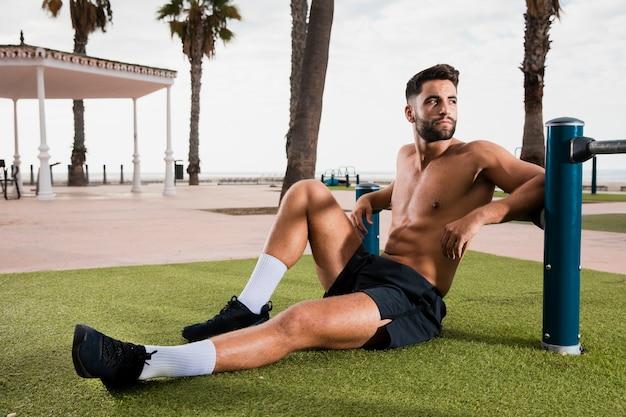 Sportmann, der auf dem gras nachdem dem laufen sitzt Kostenlose Fotos