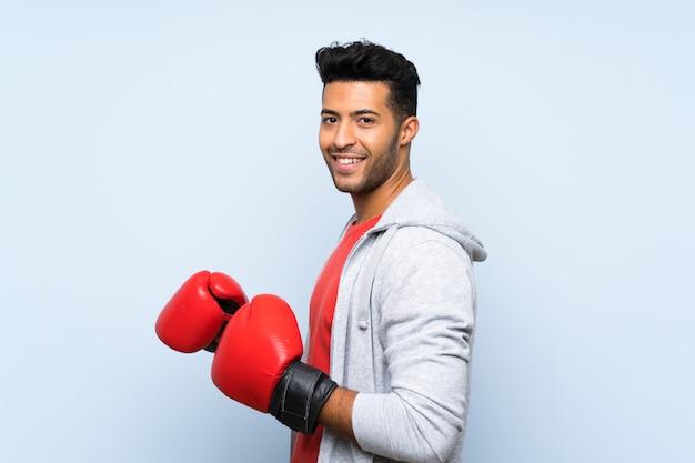 Sportmann mit boxhandschuhen über lokalisierter blauer wand Premium Fotos