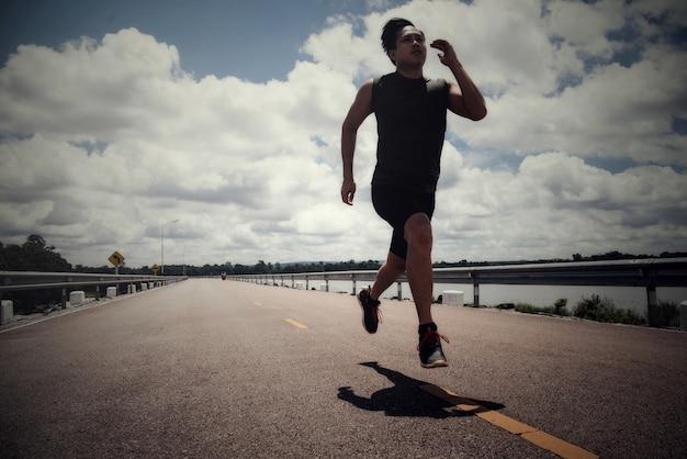Sportmann mit läufer auf der straße läuft für die übung Kostenlose Fotos