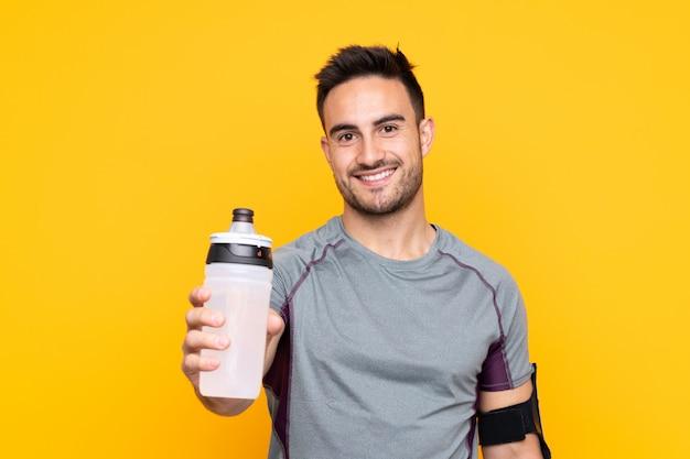 Sportmann über gelber wand mit sportwasserflasche Premium Fotos