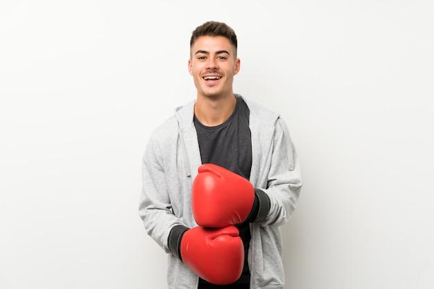 Sportmann über lokalisierter weißer wand mit boxhandschuhen Premium Fotos