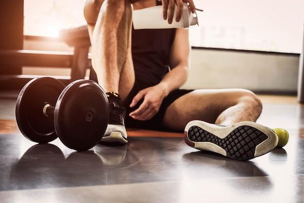 Sportmannübung und -training in der eignungsturnhalle. mann entspannen sich und proteinerschütterungsflasche und -apfel halten Premium Fotos