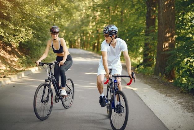 Sportpaar, das fahrräder im sommerwald reitet Kostenlose Fotos