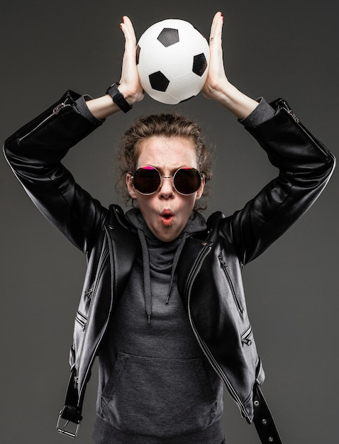 Sportwetten-konzept. überraschtes stilvolles mädchen in einer lederjacke und einem grauen sweatshirt mit brille hält den ball über ihrem kopf auf einem dunkelgrauen hintergrund Premium Fotos