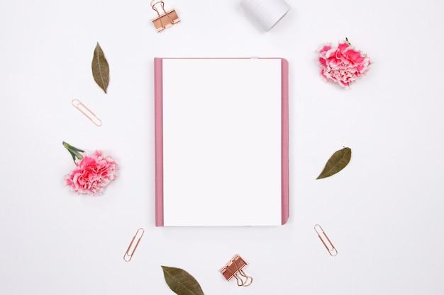 Spott herauf tagebuch mit rosa gartennelkenblume auf weißem hintergrund. Premium Fotos