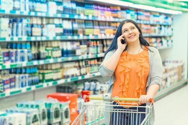 Sprechendes telefon der frau und halten des warenkorbes im supermarktspeicher nahe einkaufsfenstern. Premium Fotos