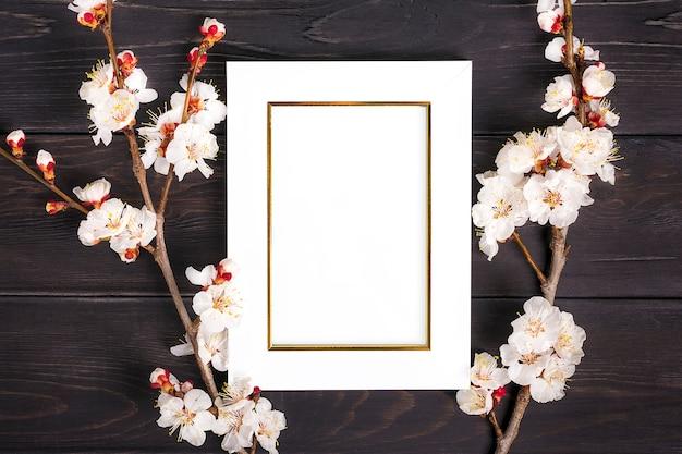 Sprigs des aprikosenbaums mit blumen und weißem fotorahmen auf hölzernem hintergrund. Premium Fotos