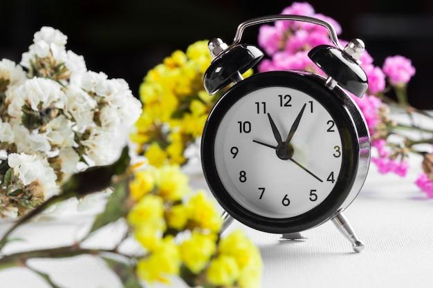 Spring time change mit wecker und blumenzweigen Premium Fotos