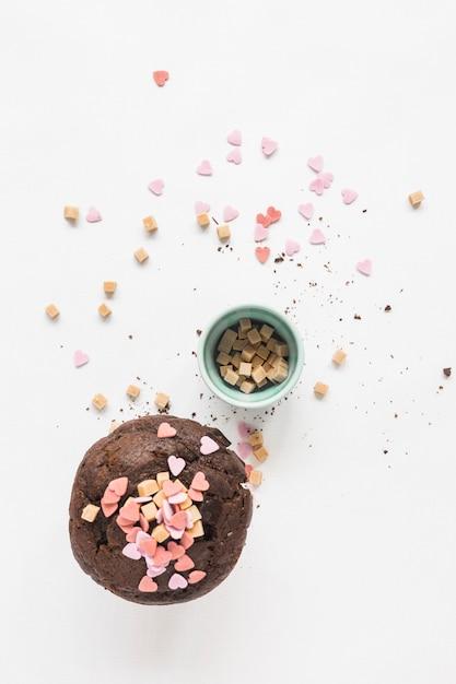 Sprinkles auf brauner kuchenschokolade über weißem hintergrund Kostenlose Fotos