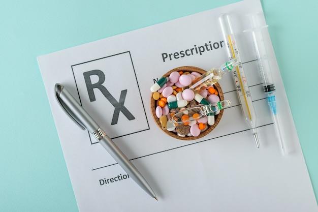Spritze, thermometer, stift und schüssel mit pillen auf einem blatt mit der verordnung eines doktors. Premium Fotos