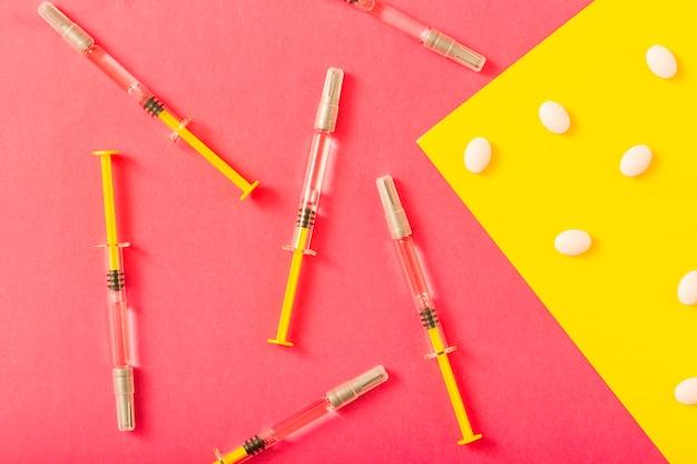 Spritze und weiße pillen über rotem und gelbem hintergrund Kostenlose Fotos
