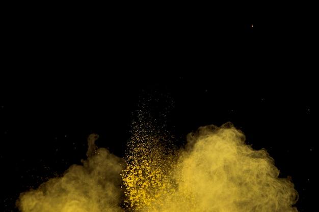 Spritzen des gelben make-uppulvers unten auf dunklem hintergrund Kostenlose Fotos