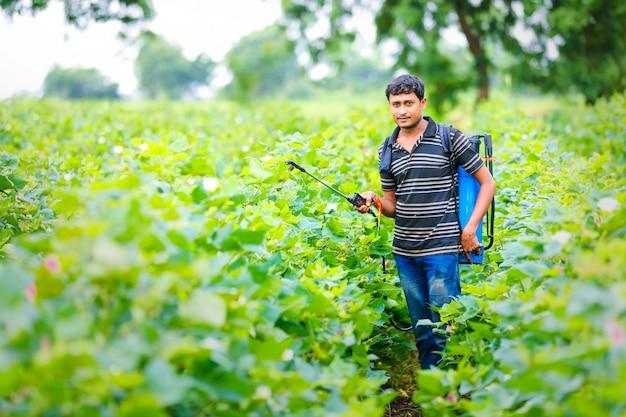Sprühpestizid des indischen landwirts am baumwollfeld Premium Fotos