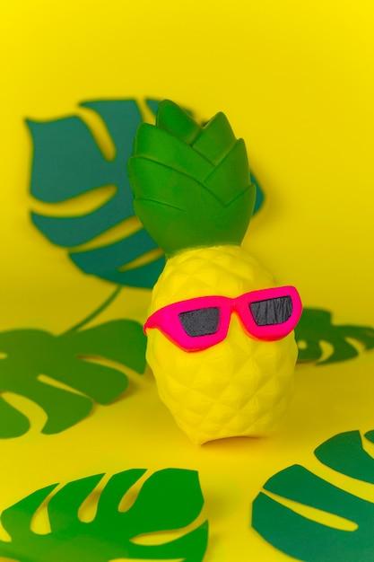 Squishy spielzeugananas in der sonnenbrille auf gelbem hintergrund unter papier schnitt tropische blätter Premium Fotos