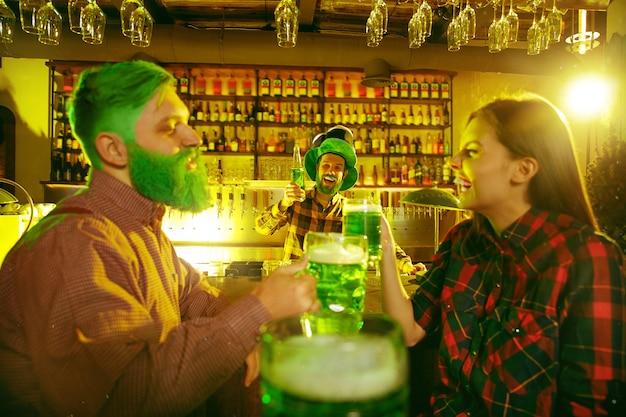 St. patrick's day party. glückliche freunde feiern und trinken grünes bier. junge männer und frauen tragen grüne hüte. pub interieur. Kostenlose Fotos