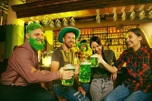 St. patrick's day party. glückliche freunde feiern und trinken grünes bier. Kostenlose Fotos