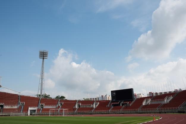 Stadionhintergrund mit einer neigung des grünen grases tagsüber Kostenlose Fotos