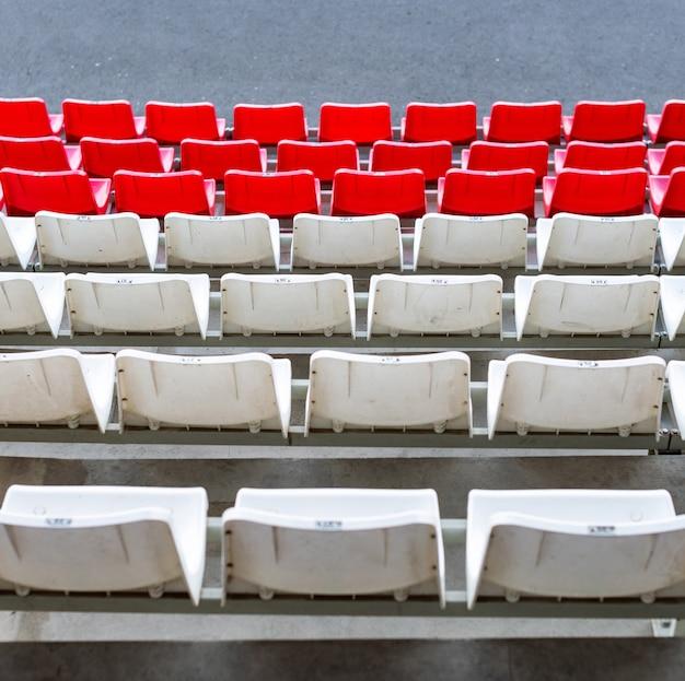 Stadionsitze, rote und weiße farbe. fußball-, fußball- oder baseballstadionstribüne ohne fans Premium Fotos