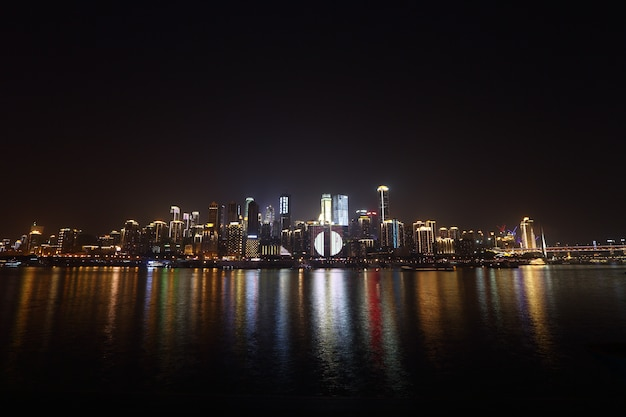 Stadt scape des himmelschabers auf flussbank und reflektieren wasser- und himmelwolke in der nachtzeit Premium Fotos