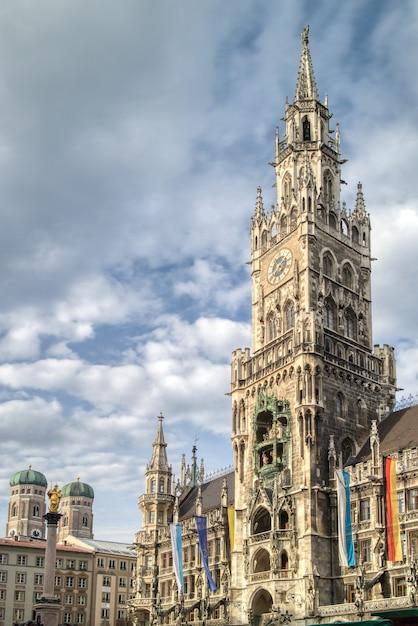 Stadtlandschaft mit hohem handtuch des zentralen gebäudes des neuen rathauses am marienplatzplatz auf einem hintergrund des blauen bewölkten himmels, münchen, bayern, deutschland Premium Fotos