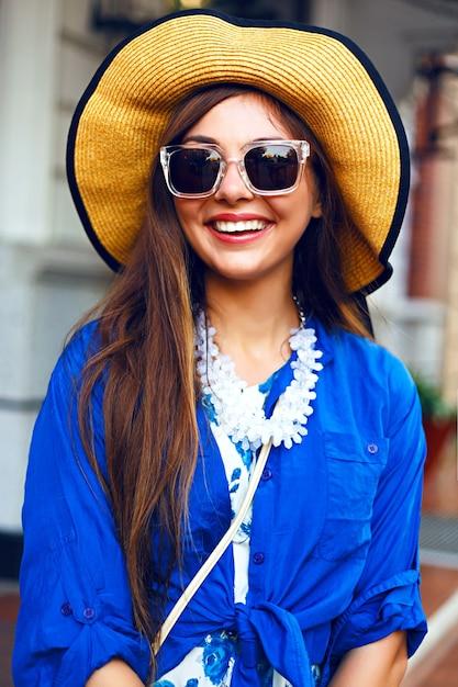 Stadtlebensstil-modeporträt des glücklichen hübschen mädchens, das allein geht, das spaß auf der straße, abendsonnenlicht, weinlesehut des retro-kleides, glückliche positive stimmung hat. Kostenlose Fotos