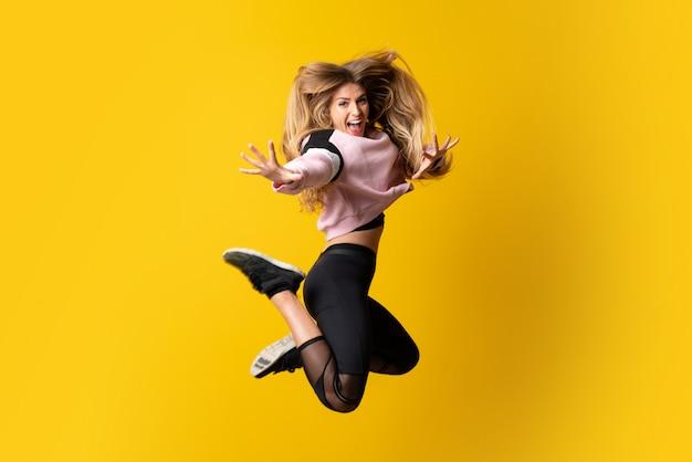 Städtische ballerina, die über lokalisierte gelbe wand und das springen tanzt Premium Fotos
