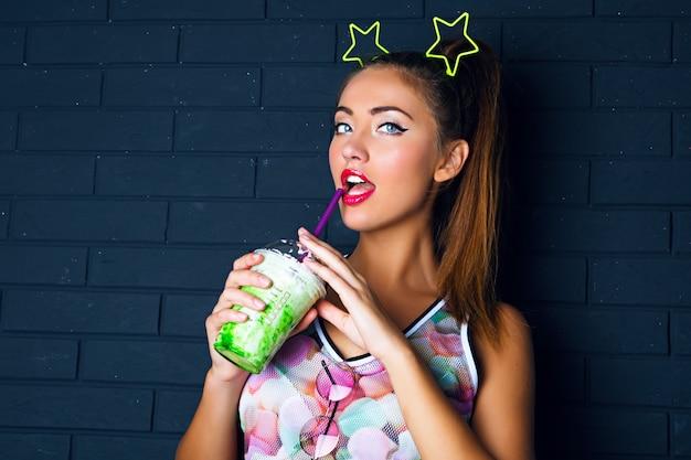 Städtisches modeporträt der brünetten frau mit hohem pferdeschwanz, trendigem make-up, bedrucktem hemd und lustigem partystern-accessoire auf ihrem kopf tragendem süßem grünem milchshake im urbanen stil. Kostenlose Fotos