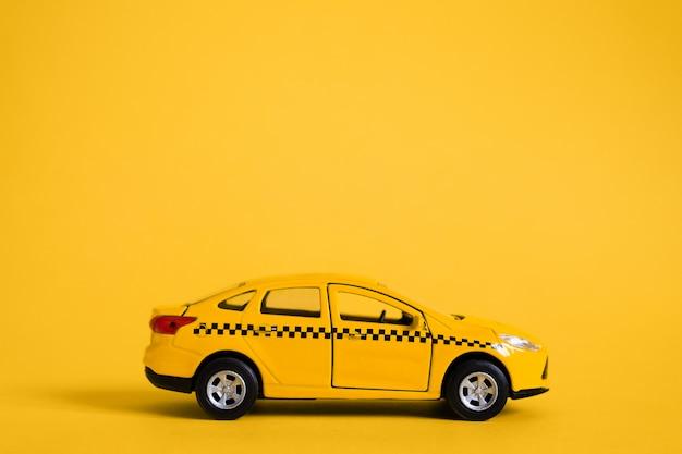 Städtisches taxi und lieferservice-konzept. spielzeug gelbes taxi-automodell. kopieren sie platz für text, banner. online-taxi-service für mobile anwendungen bestellen. Premium Fotos