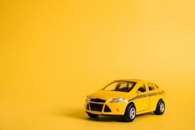 Städtisches taxi und lieferservice-konzept. spielzeug gelbes taxi-automodell Premium Fotos