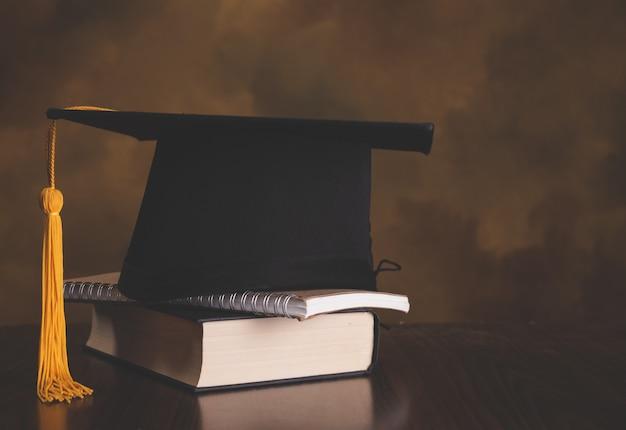 Staffelungskappe auf büchern treten in bibliotheksraum des campus und der universität, konzept von internationalem pädagogischem im ausland, zurück zu schule Premium Fotos