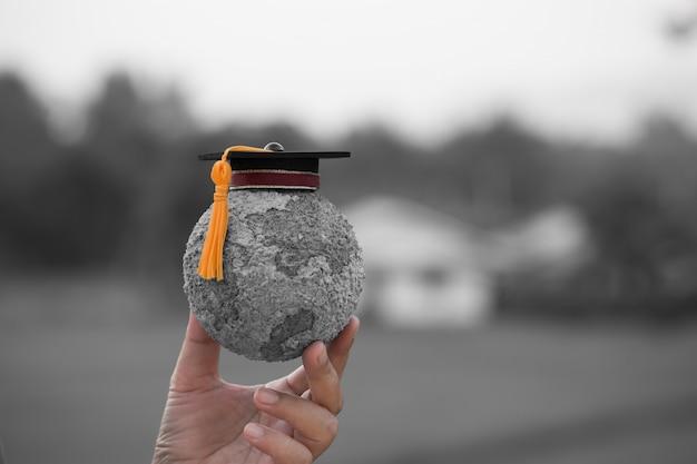 Staffelungskappe auf den studenten, die graue pappmachéhandwerks-erdkugel halten Premium Fotos