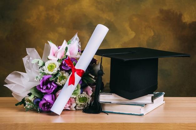 Staffelungskappe, hut mit gradpapier und blumenblumenstrauß auf hölzerner tabelle. Premium Fotos